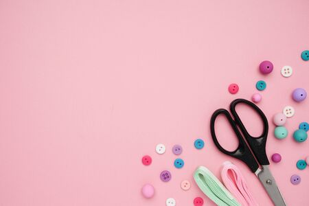 Collection of Colourful Sewing Buttons and Scissors on Pink Background with Copy Space Zdjęcie Seryjne