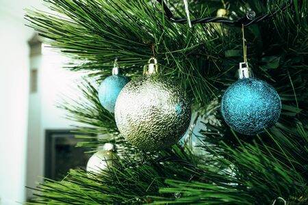 Christmas tree with blue and silver decorations in a bright room side view Zdjęcie Seryjne