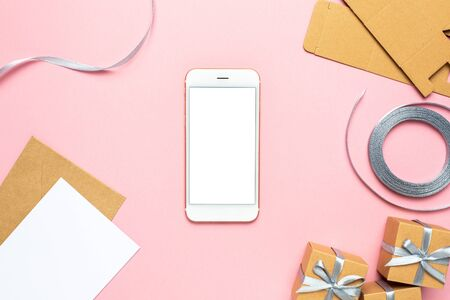 Mobile phone with gift in box composition for birthday on pink background top view Zdjęcie Seryjne