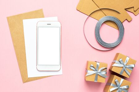 Mobile phone and white card with gift in box composition for birthday on pink background top view