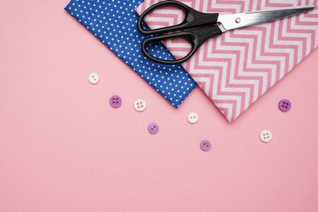 Scissors,fabrics and buttons for sewing on pink background with copy space top view Zdjęcie Seryjne