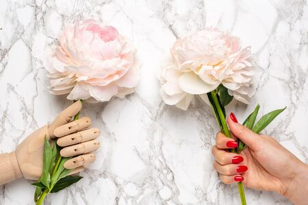 Wooden mannequin hand and female hand with piony flower on marble background flat lay