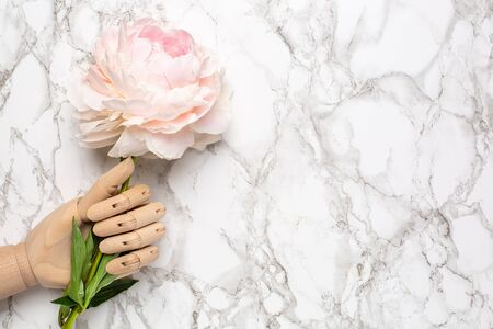 Wooden mannequin hand with piony flower on marble background flat lay