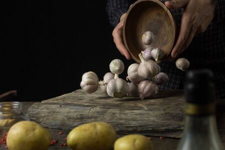 Man preparing a dish with garlic and potatoes in the kitchen on a rustic wooden table side view