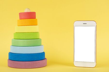 Baby multi-colored pyramid and mobile phone mock up on yellow background side view