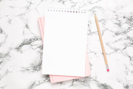 White and pink notebook on a marble background top view 写真素材