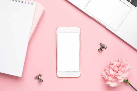 Mobile phone with pink carnation flower on a marble background top view Stock Photo
