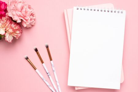 White and pink notebook with carnation flower and make up brushes on a pink background