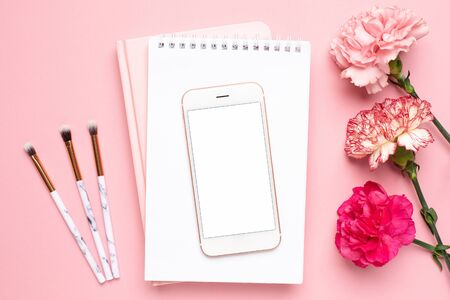 White notebook and mobile phone with carnation flower on a pink background Stock Photo