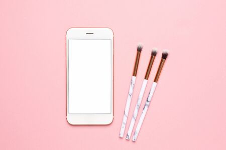 Mobile phone and beauty make up brushes on a pink background Reklamní fotografie