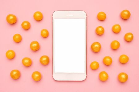 Mobile phone and sweet yellow candies on a pink background top view