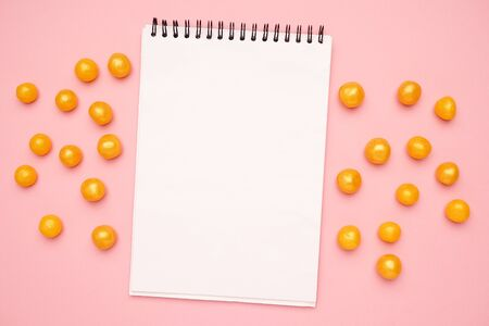 White notebook and sweet yellow candies on a pink background top view