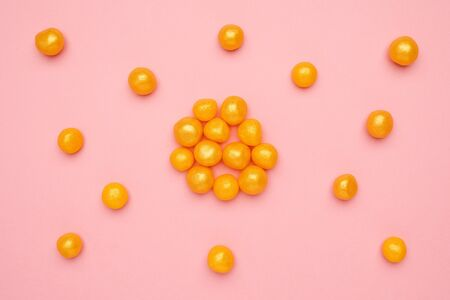 Sweet yellow candies on a pink background, round sweet food top view