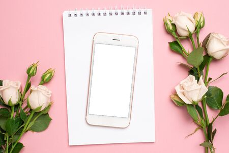 Mobile phone with a white notebook and roses flowers on pink background Stok Fotoğraf