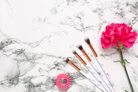 Beautiful pink flower with make up brushes on marble background