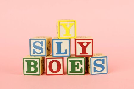 Toy colored cubes with letters on pink background side view