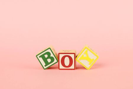 Colored cubes with letters Boy on a pink background side view Stock Photo