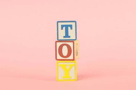 Colored cubes with letters with the inscription Toy on a pink background side view