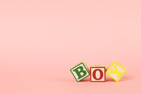 Pink backgrod and colored cubes with letters Boy, children toy side view