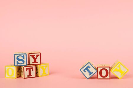 Pink background and toy colored cubes with letters side view