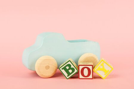 Colored cubes with letters Boy and toy car on a pink background side view