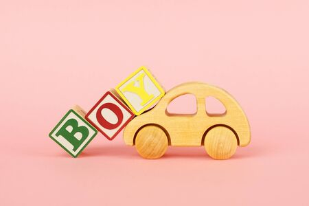 Colored cubes with letters Boy and car toy on a pink background side view