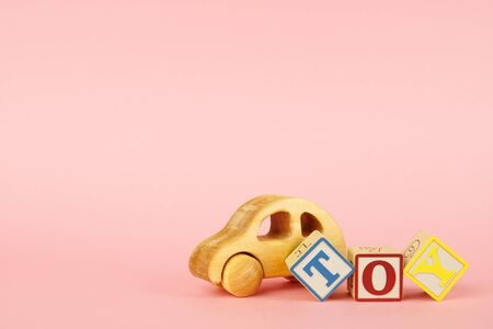 Pink background with colored cubes with letters toy and toy car side view
