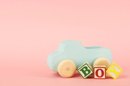Pink background with colored cubes with letters Boy and toy car side view