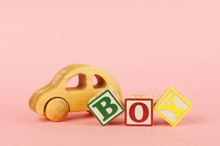 Colored cubes with letters Boy and toy car on a pink background Stock Photo