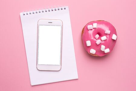 Mobile phone and sweet pink donut with marshmallows on a pink background flat lay Reklamní fotografie