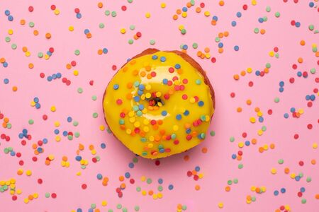 Sweet yellow donut with sprinkle on a pink background flat lay top view Stok Fotoğraf