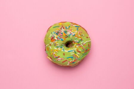 Sweet green donut with sprinkle on a pink background flat lay top view