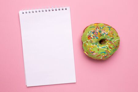 Notebook and sweet green donut with sprinkle on a pink background flat lay top view Stok Fotoğraf