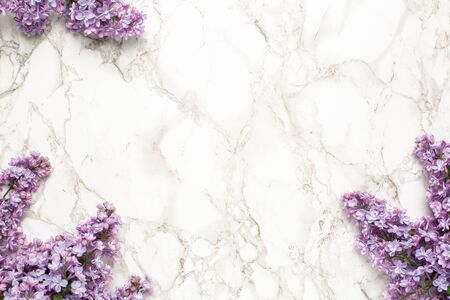Purple lilac flowers on marble background, simple composition for holiday top view Stockfoto