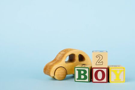 Blue background with colored cubes with letters Boy and toy car side view, giving birth to a baby boy, toys for toddlers