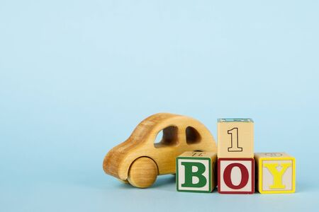 Blue background with colored cubes with letters Boy and toy car side view, giving birth to a baby boy, toys for toddlers Reklamní fotografie - 132243936