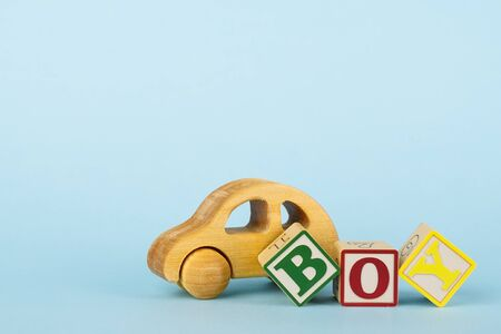 Blue background with colored cubes with letters Boy and wooden toy car, giving birth to a baby boy, toys for toddlers side view