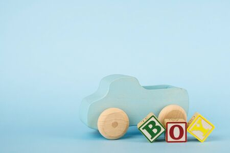 Blue background with colored cubes with letters Boy and wooden toy car side view, giving birth to a baby boy, toys for toddlers