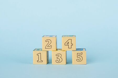 Wooden childrens cubes on a blue background side view, early childhood development and education 写真素材 - 132245375