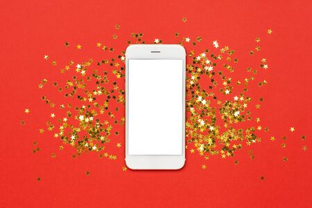 Mobile phone with golden stars confetti on red color paper background minimal style, christmas and new year concept Stock Photo