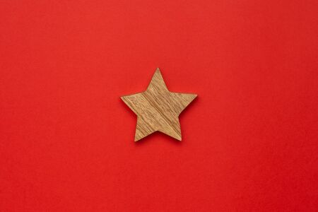 Wooden decoration star for Chrismas tree on red color background Foto de archivo - 133414931