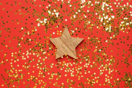 Wooden decoration star with golden stars confetti on red color background top view Foto de archivo - 133414936