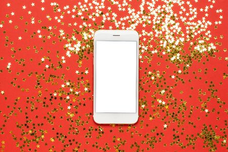Mobile phone with golden stars confetti on red color paper background top view