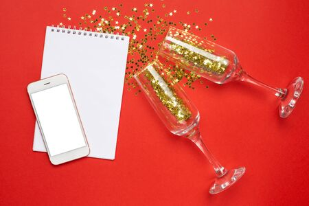 Mobile phone, notepad and champagne glasses with golden stars confetti on red color paper background minimal style Stock Photo