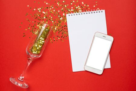 Mobile phone, notepad and champagne glasses with golden stars confetti on red color paper background minimal style, christmas and new year concept top view
