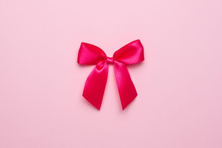 Pink gift satin ribbon bow on pastel pink background top view 版權商用圖片