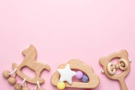 Baby wooden rattles and toys on pink background isolated with copy space top view