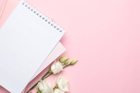 Beautiful white eustoma flower and notebook on pink background with copyspace top view.