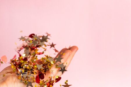 Gold and red confetti in women's hand on pastel pink background side view. Bright and festive holiday background.
