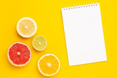 Notebook and tropical cutting citrus fruits , orange and lime on yellow background with copyspace top view Imagens